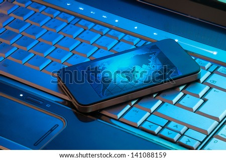 Computer keyboard and cellphone in a beautiful shade of blue - stock photo