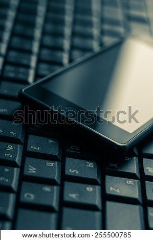 Computer keyboard and cellphone in a beautiful shade of blue. - stock photo