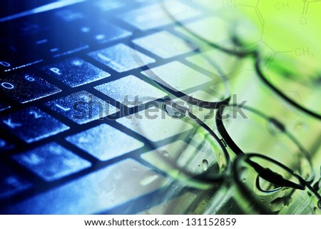 Computer keyboard and laboratory glass. Science concept. - stock photo