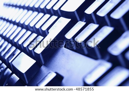 Computer keyboard close-up in blue light. Shallow DOF! - stock photo