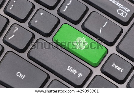 Computer keyboard closeup with dollar sign on green enter key