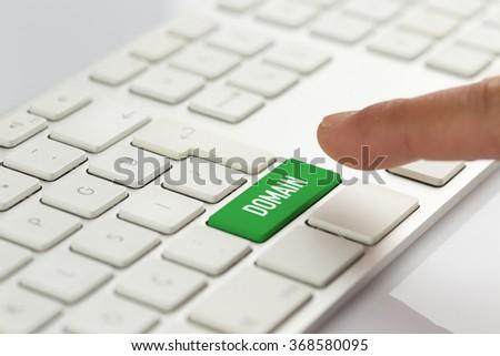 Computer Keyboard Concept: Hand pushing green DOMAIN keyboard button - stock photo