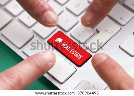 Computer Keyboard Concept: Many fingers pushing red REAL ESTATE keyboard button - stock photo