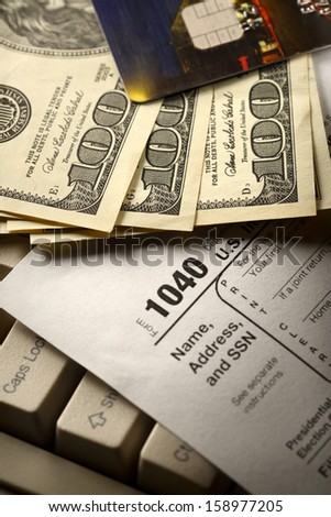 Computer keyboard, credit cards, tax form and dollars in cash - stock photo