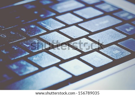 Computer keyboard in blue light. Small depth of field. Toned image. - stock photo