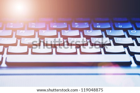 Computer keyboard in light. Small depth of field. - stock photo