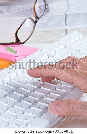Computer keyboard on desk with folders and work related items, shallow depth of field, focus on first finger - stock photo