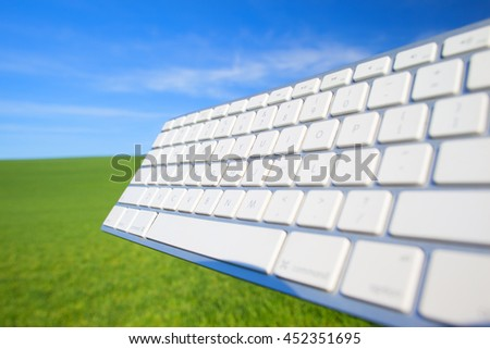 Computer keyboard on sky and grass background - stock photo