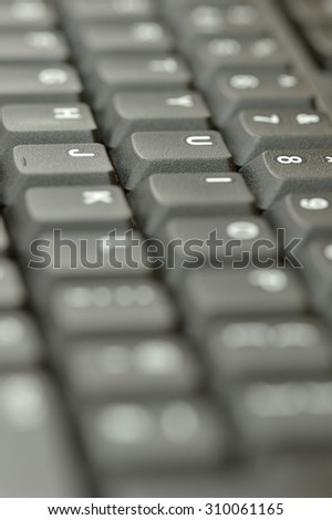 Computer keyboard. Vertical close up of mostly blurred bands of keys in grey.