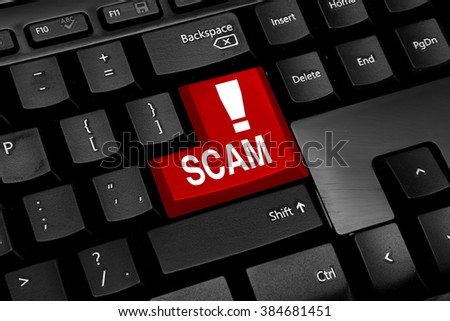 Computer keyboard with red scam button - stock photo