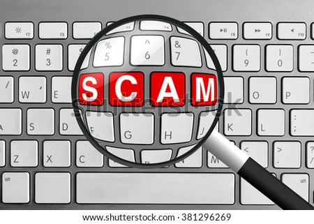 Computer keyboard with red scam buttons and magnifying glass - stock photo