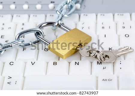 Computer keyboard with silver chain, padlock and keys relating to computer security or parental control over internet access.