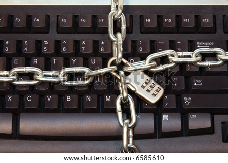 Computer Keyboard wrapped with lock and chains to prevent unwanted access, computer hacking, theft and piracy - stock photo