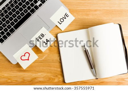 computer, laptop keyboard with notice that february 14 is Valentine's day. Reminder with sticky papers with love, don't forget and red heart symbol and with notebook for list of presents - stock photo