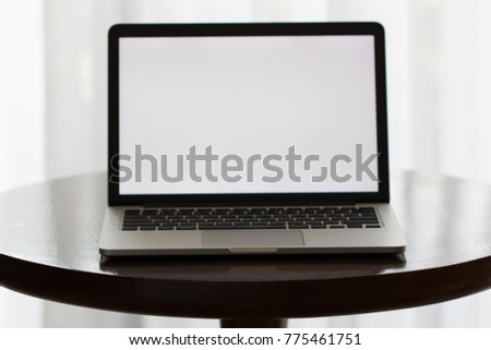 Computer laptop with white blank screen on wooden round table in living room with white curtain background, concept of technology or digital business lifestyle