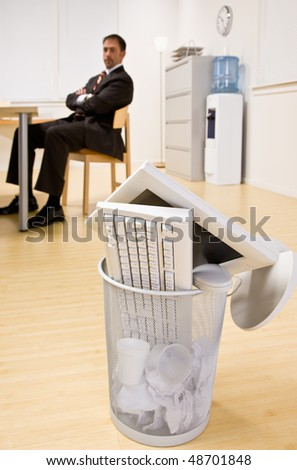 Computer monitor and keyboard in trash basket - stock photo