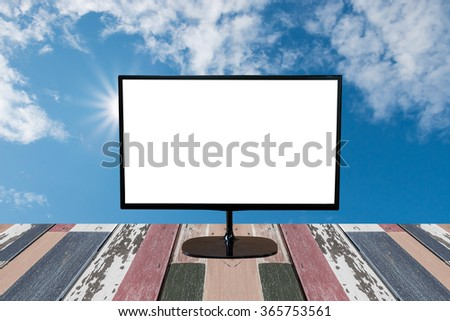 computer monitor with blank screen on wooden empty brown table on Blue sky with clouds and sun - stock photo