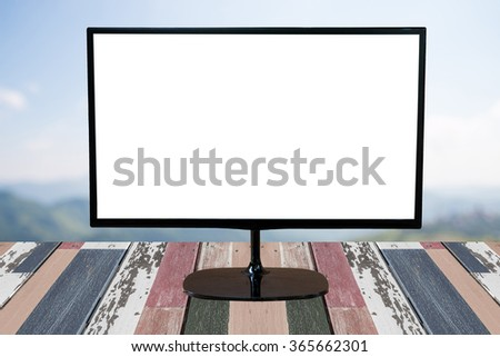 computer monitor with blank screen on wooden empty brown table on  natural  blurred background - stock photo