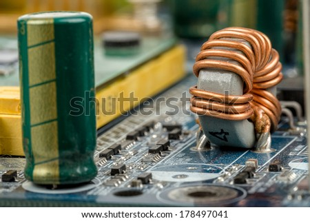computer motherboard, detail of capacitor with shallow focus - stock photo