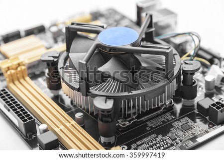 Computer motherboard with CPU cooler on white background.