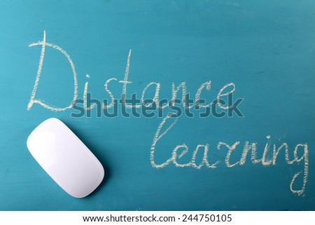 Computer mouse and inscription Distance Learning on blackboard background - stock photo