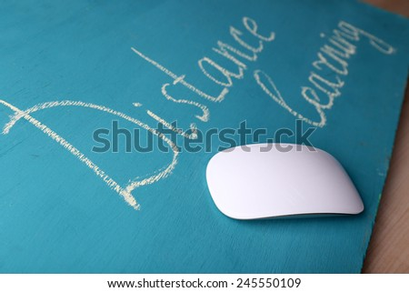 Computer mouse and inscription Distance Learning on blackboard on wooden table background - stock photo