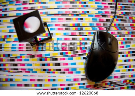 Computer mouse and printing loupe, focus on CMYK strips. Prepress color menagement in print production concept. - stock photo