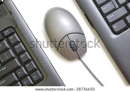 Computer mouse between two laptops - stock photo