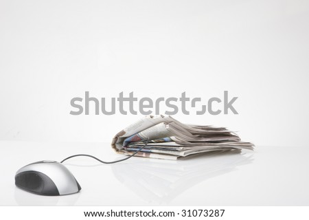 computer mouse connected to newspaper - stock photo
