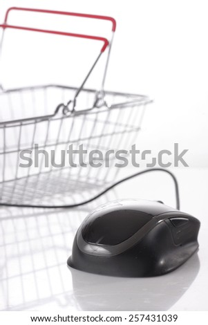 Computer mouse connected to shopping basket on white background - stock photo
