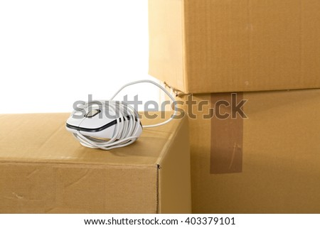 Computer mouse on moving boxes over white background - office moving or relocation concept - stock photo