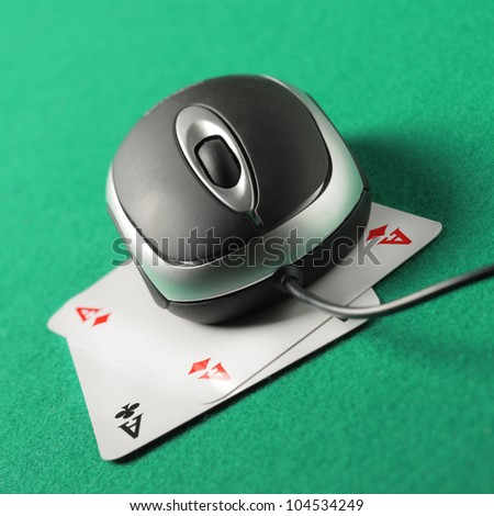 Computer mouse on top of a pair of aces - stock photo