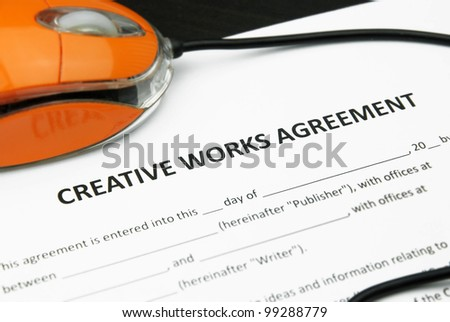 Computer Mouse with Creative Works Agreement Document - stock photo