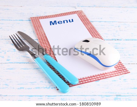 Computer mouse with menu and cutlery on wooden background - stock photo