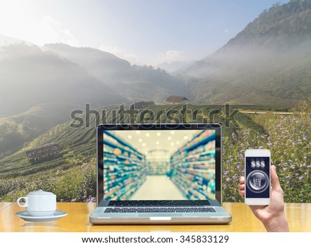 Computer notebook with holding smart mobile on Tea field when sunrise with fog, show Abstract blurred photo of store with trolley in department store bokeh background, online shopping concept