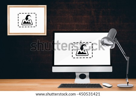 Computer on a desk against a dark wall - stock photo