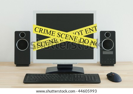 Computer on a desk with a Crime Scene label. - stock photo