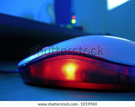 computer optical mouse glowing with red light in the office - stock photo