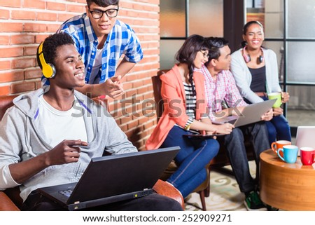 Computer programmer in start-up company coding, co-worker is looking over his shoulder - stock photo