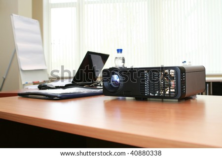 Computer projector and laptop on table in boardroom