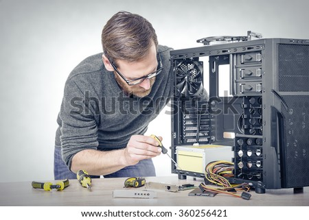 Computer repair. Computer technician working on a personal computer. Toned photo. - stock photo