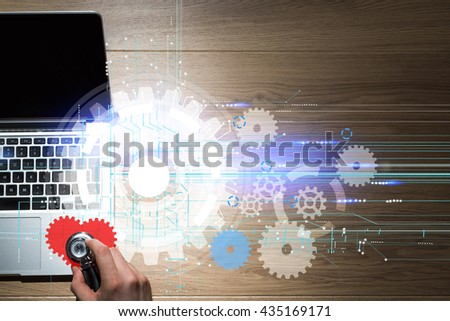 Computer repair service with hand listening to abstract laptop heartbeat with digital cogweel pattern on wooden desktop - stock photo