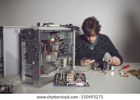 Computer Repair: young man using cellphone - stock photo