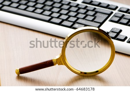 Computer security concept with keyboard and magnifying glass - stock photo