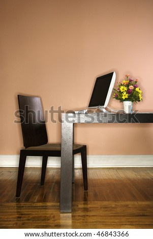 Computer sitting on a table with a vase of colorful flowers on it. Vertical shot. - stock photo