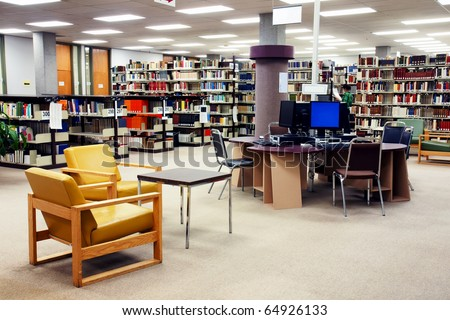 Computer station at the university college library with seating area in the foreground. One young female student searching far in the background. - stock photo