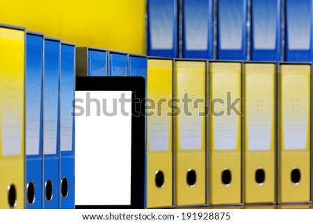 Computer Tablet out of a row of binders.  - stock photo