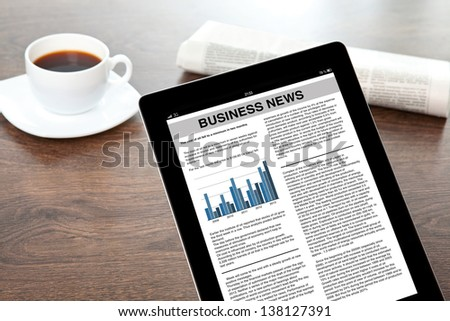 computer tablet with business news in a screen on a table at a businessman in office - stock photo