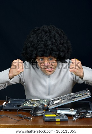 computer technician is trying to repair a laptop - stock photo