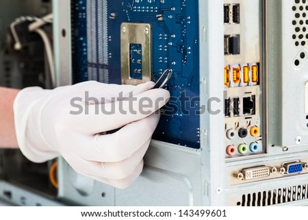 Computer technician using tweezers to repair circuit - stock photo